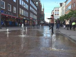 In der Fußgängerzone am Rathaus in Lübeck freuen sich besonders die Kinder über die Wasserdüsen.